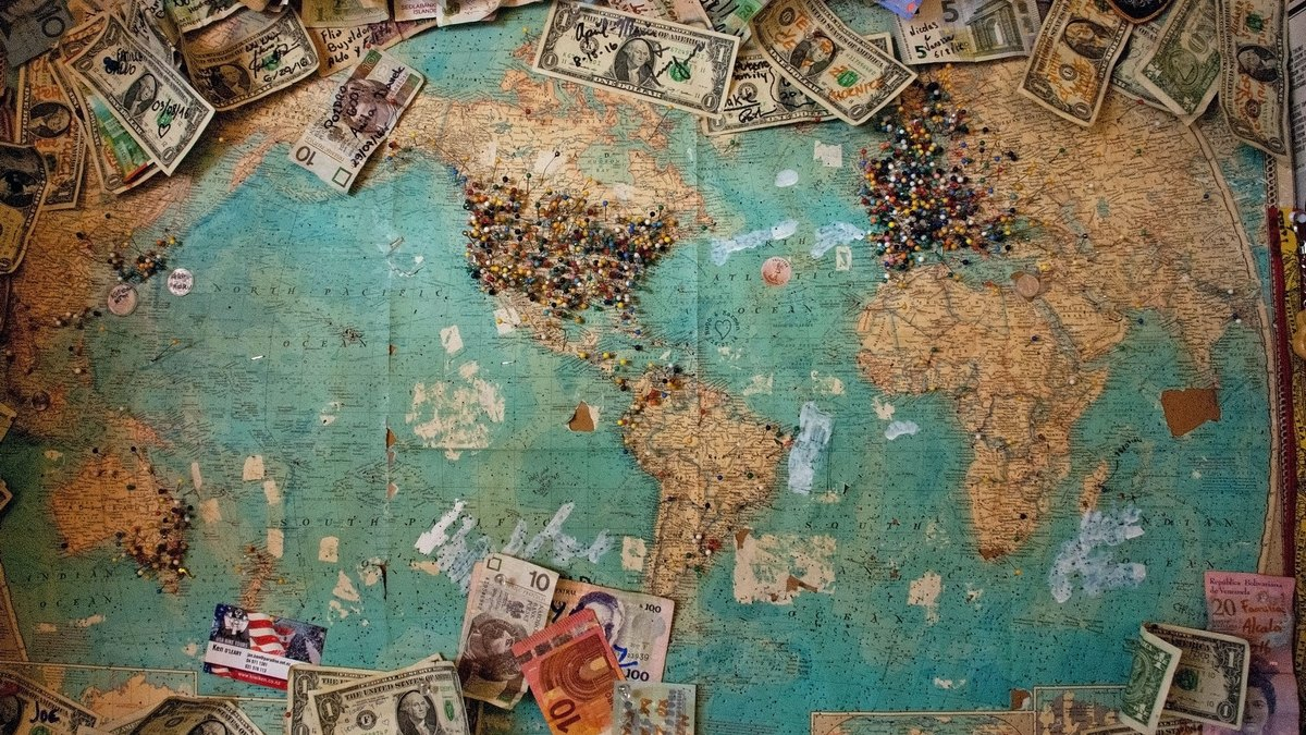 Mapa świata z rozrzuconymi pieniędzmi