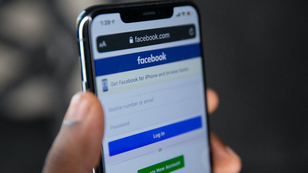 Mężczyzna ze samrtfonem z uruchomionym Facebookiem